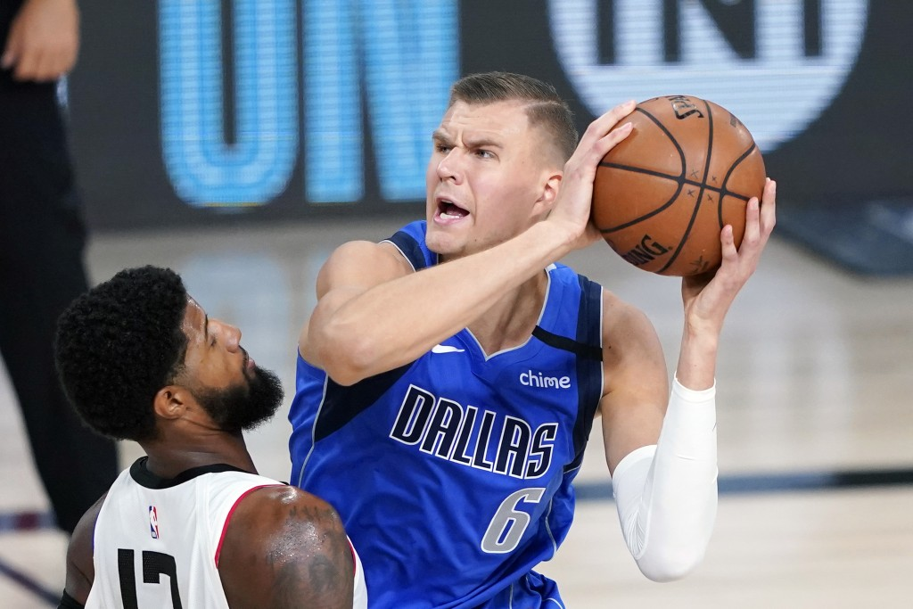 FILE - Dallas Mavericks' Kristaps Porzingis (6) is defended by Los Angeles Clippers' Paul George (13) during the first half of an NBA basketball first...