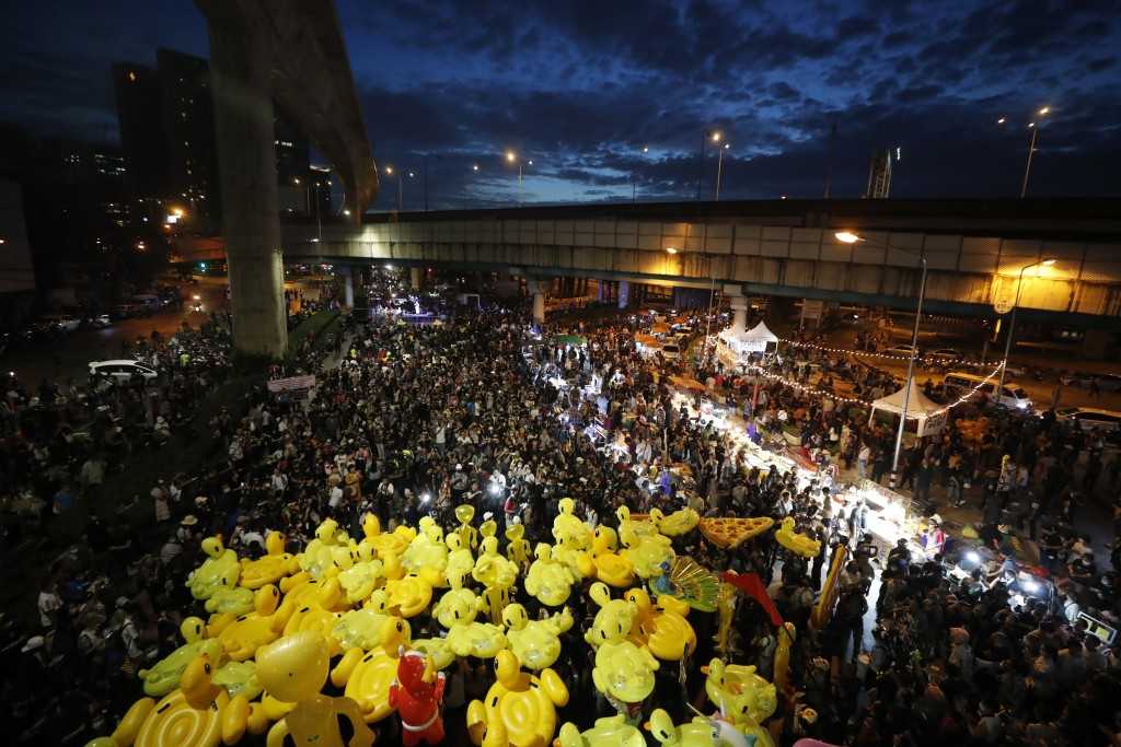 Inflatable yellow ducks, which have become good-humored symbols of resistance during anti-government rallies, are lifted over a crowd of protesters Fr...