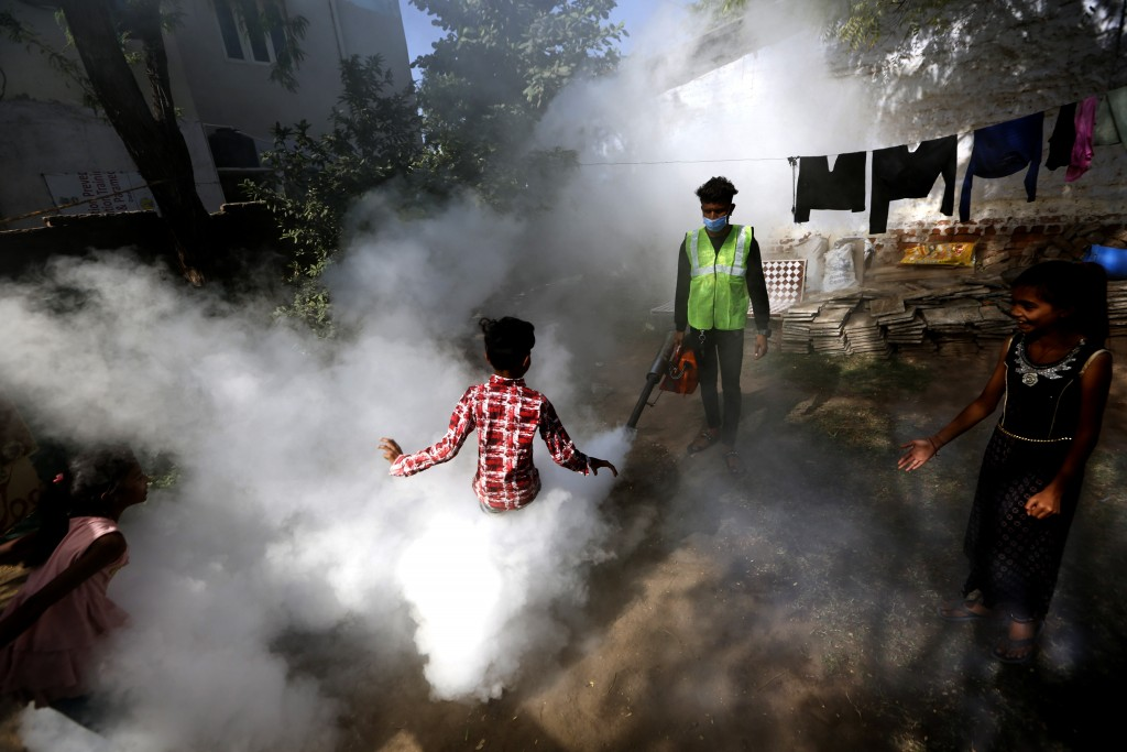 A boy plays smoke from fumigation being carried out by a municipal worker at a residential area in Ahmedabad, India, Thursday, Dec. 3, 2020. (AP Photo...