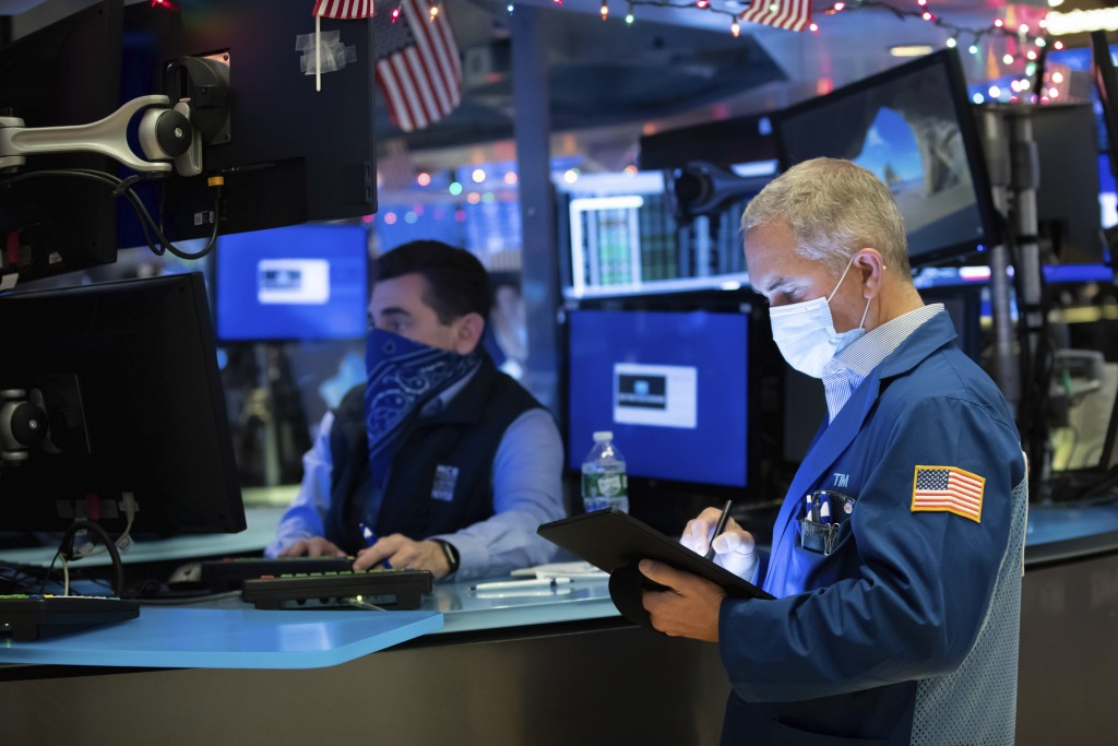 In this photo provided by the New York Stock Exchange, trader Timothy Nick, right, works on the floor, Thursday Dec. 3, 2020. U.S. stocks are inching ...