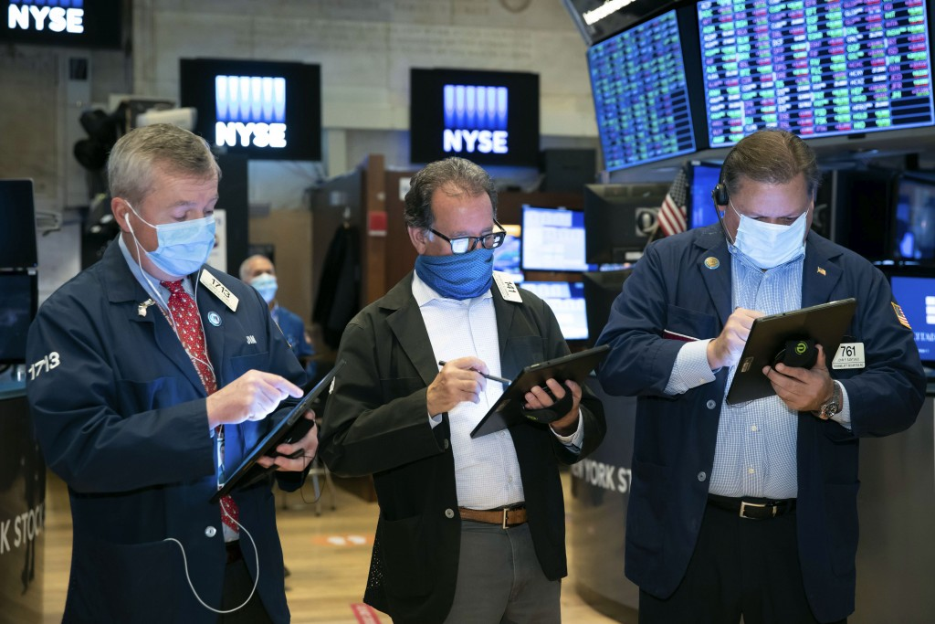 In this photo provided by the New York Stock Exchange, traders James Lamb, Sal Suarino and John Santiago, left to right, work on the trading floor, Th...