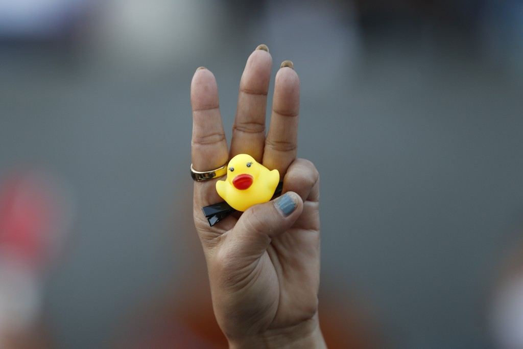 The three-finger protest gesture is flashed by a protester while holding a yellow duck, which has become a good-humored symbol of resistance during an...