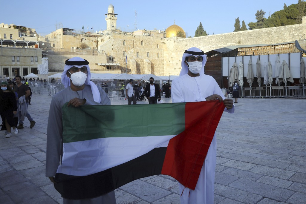 Emirati singer Walid Aljasim, left, and an unidentified companion pose for a photo with the flag of the United Arab Emirates during their visit in Jer...