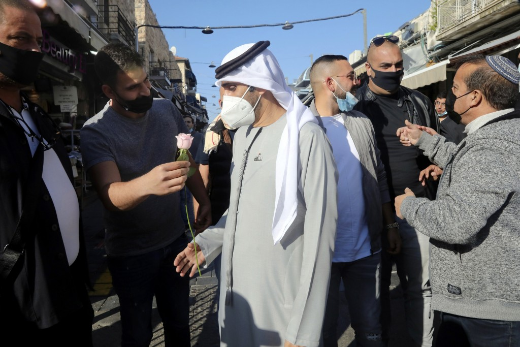 An Israeli man handed a flower to Emirati singer Walid Aljasim, during his visit in Jerusalem, Thursday, Dec. 3, 2020. (AP Photo/Mahmoud Illean)