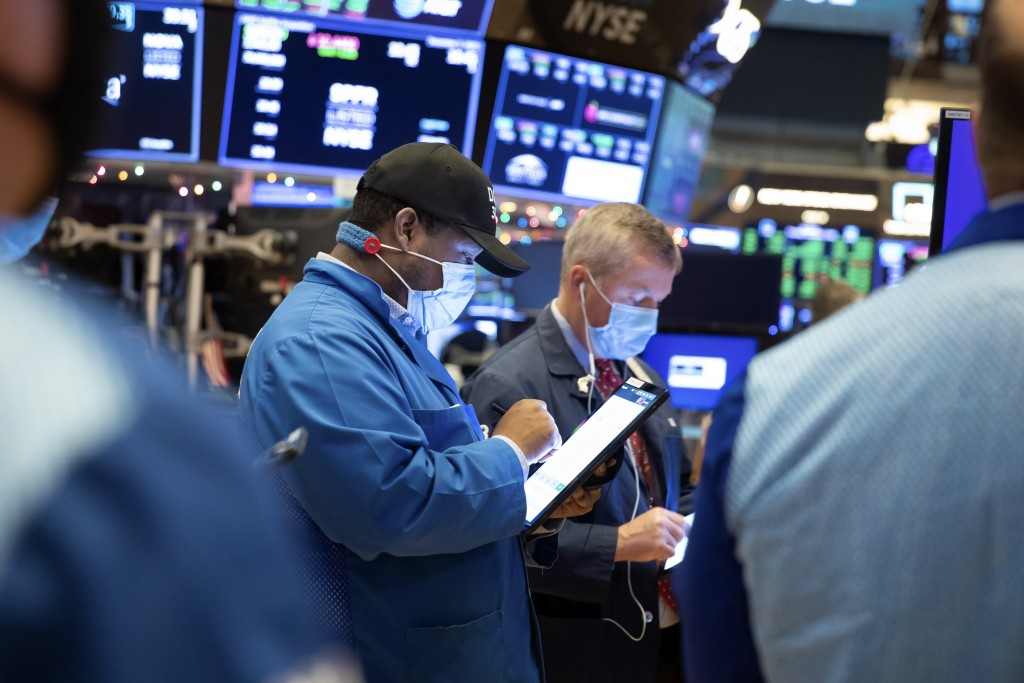 In this photo provided by the New York Stock Exchange, traders work on the floor, Thursday Dec. 3, 2020. U.S. stocks are inching further into record h...
