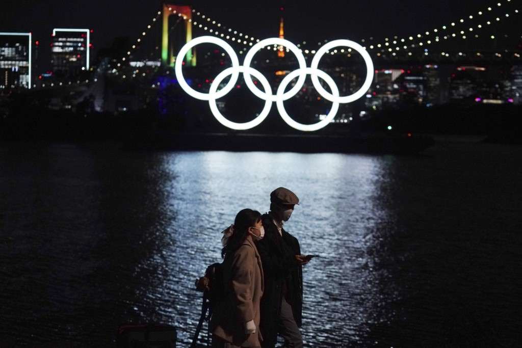 A man and a woman walk past near the Olympic rings floating in the water in the Odaiba section Tuesday, Dec. 1, 2020, in Tokyo. The Olympic Symbol was...
