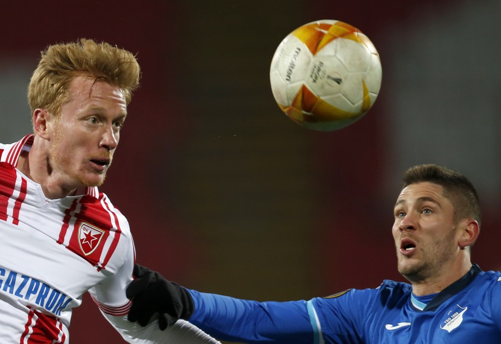 Red Star's Radovan Pankov, left, jumps for the ball with Hoffenheim's Andrej Kramaric during the Europa League group L soccer match between Red Star a...