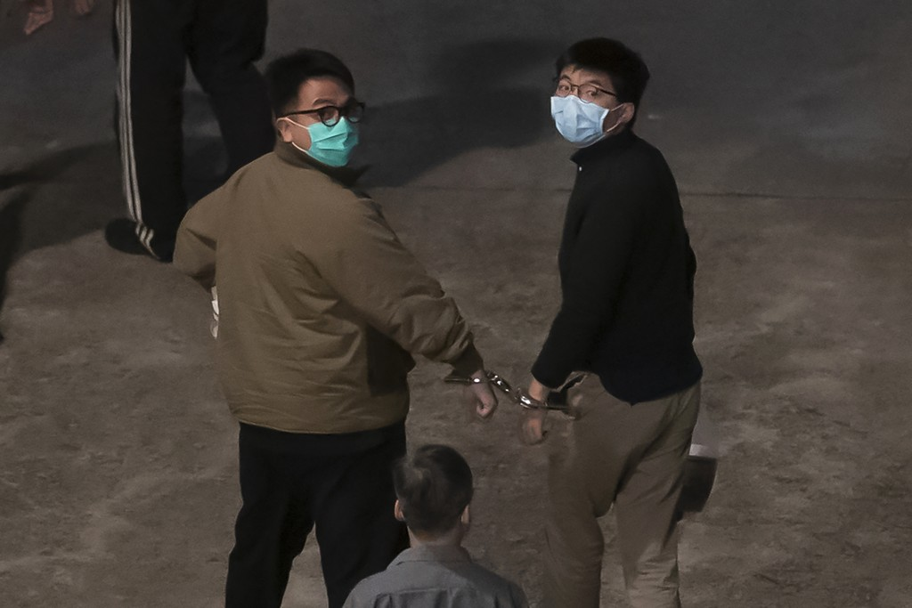 Hong Kong activists Joshua Wong, right, and Ivan Lam, left, are escorted by Correctional Services officers to prison, in Hong Kong, Wednesday, Dec. 2,...