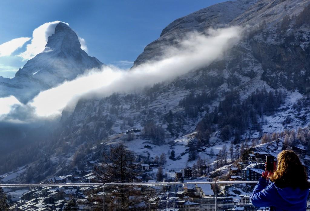 A woman takes a picture the Matterhorn, left, in Zermatt, Switzerland, Wednesday, Dec.2, 2020. Zermatt is home to one of the Swiss ski stations that h...
