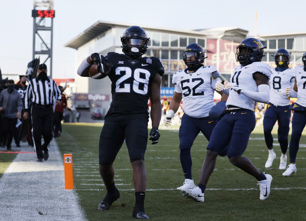 Iowa State running back Breece Hall, left, runs in a touchdown as West Virginia defensive lineman Jalen Thornton, center, and cornerback Nicktroy Fort...