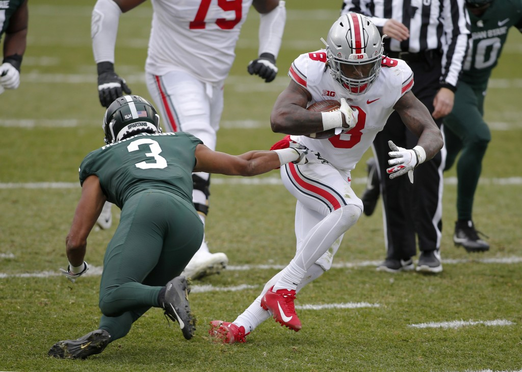 Ohio State's Trey Sermon, right, rushes against Michigan State's Xavier Henderson (3) during the first half of an NCAA college football game, Saturday...
