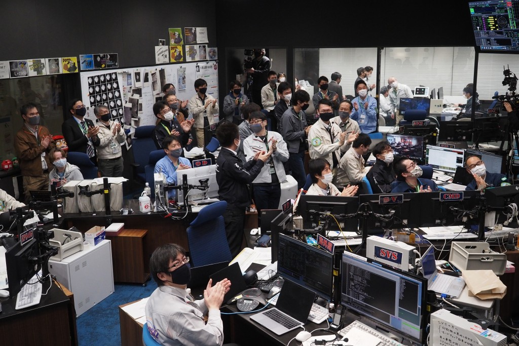 In this photo provided by the Japan Aerospace Exploration Agency (JAXA), Hayabusa2 project members react as they watch over the live streaming about t...
