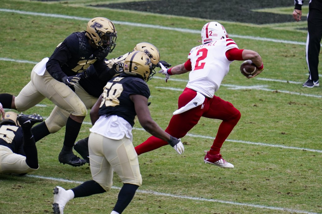 Nebraska quarterback Adrian Martinez (2) breaks away from Purdue defenders on his way to a touchdown during the first quarter of an NCAA college footb...