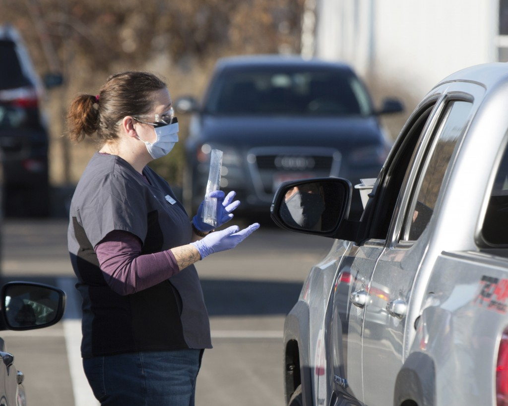 An employee gives instructions for self-administering a COVID-19 test in the parking lot at Primary Health Medical Group's clinic in Boise, Idaho, Tue...