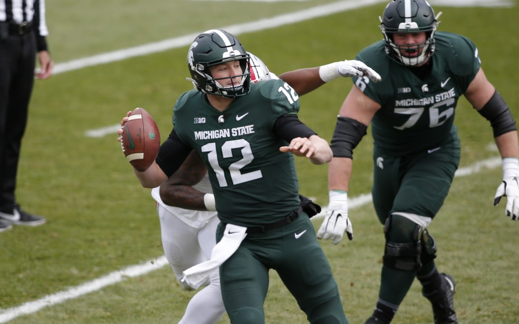Michigan State quarterback Rocky Lombardi (12) is sacked by Ohio State's Tyreke Smith, rear, during the first half of an NCAA college football game, S...