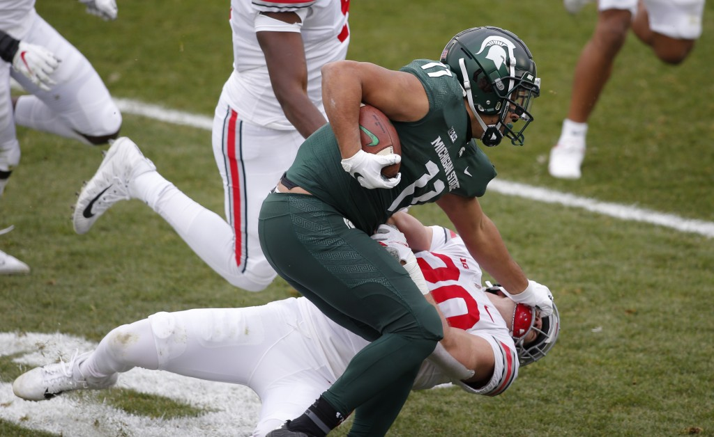 Michigan State running back Connor Heyward (11) stiff arms Ohio State linebacker Pete Werner during the first half of an NCAA college football game, S...
