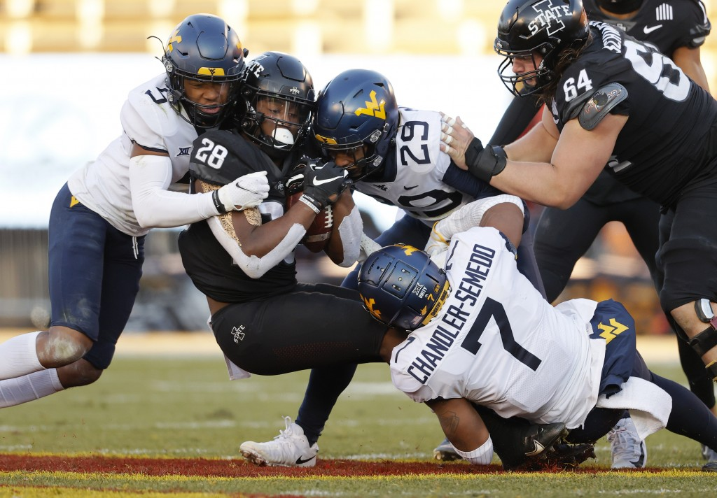 Iowa State running back Breece Hall, center, fights for yards as he is swarmed by West Virginia cornerback Dreshun Miller, left, safety Sean Mahone, r...