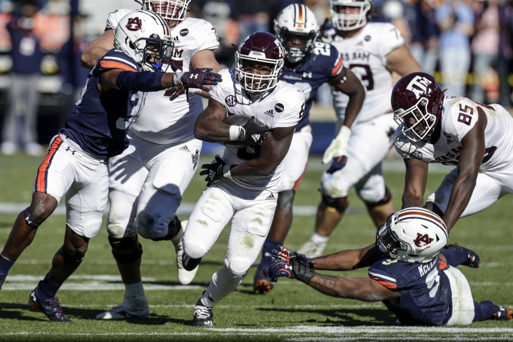 Texas A&M running back Devon Achane (6) carries the ball as Auburn defensive back Jaylin Simpson (36) and linebacker Zakoby McClain (9) try and stop h...