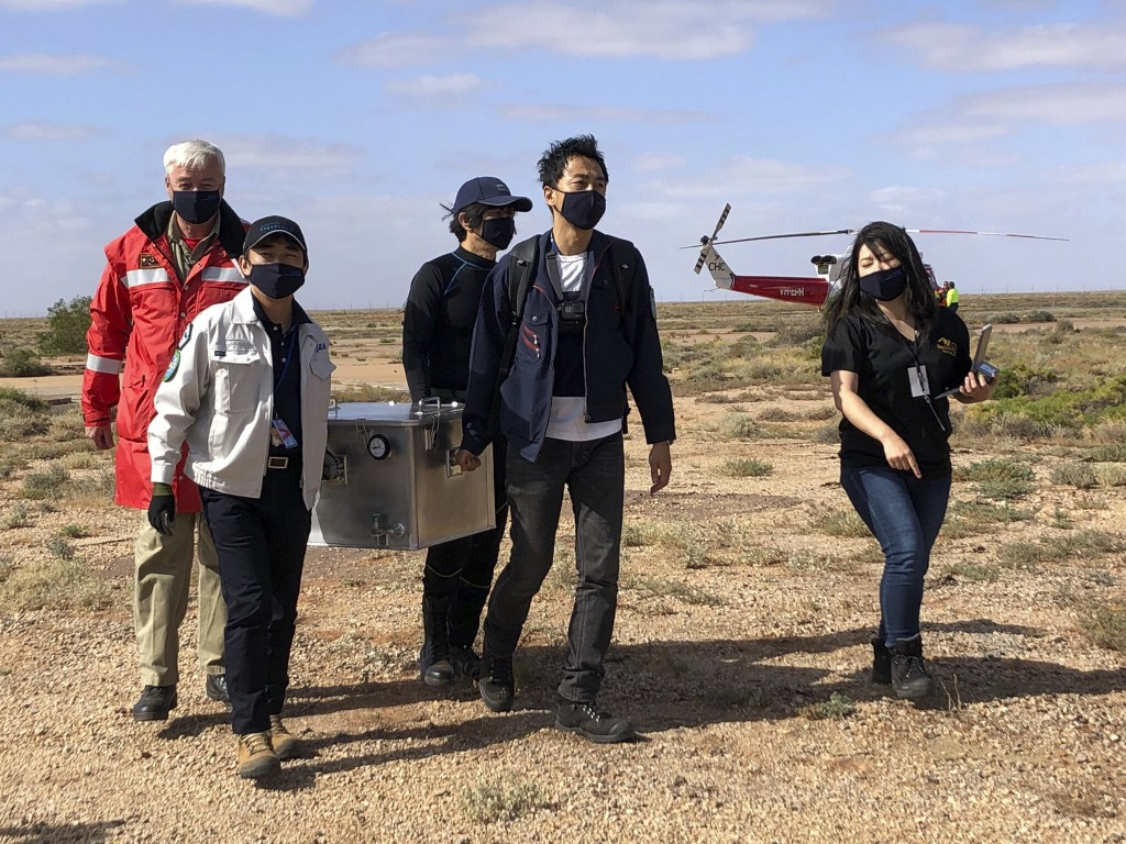 In this photo provided by the Australian Space Agency, members of the Japan Aerospace Exploration Agency (JAXA) arrive at a range support facility in ...