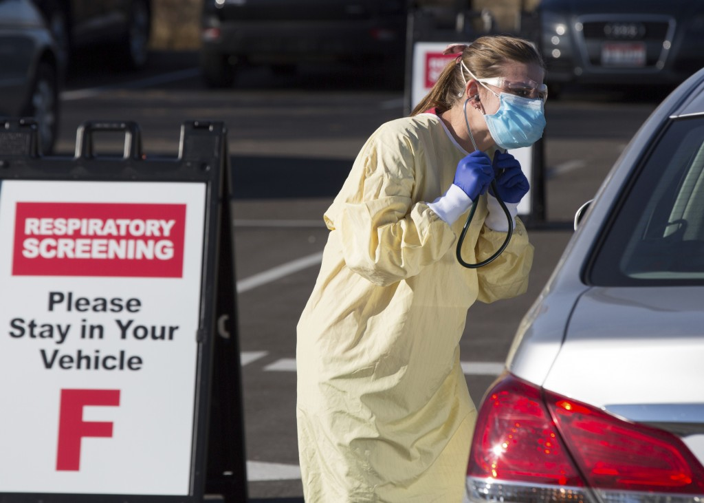 Physician assistant Nicole Thomas conducts a COVID-19 examination in the parking lot at Primary Health Medical Group's clinic in Boise, Idaho, Tuesday...