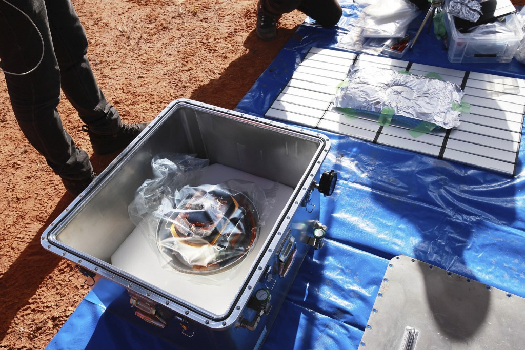 In this photo provided by the Japan Aerospace Exploration Agency (JAXA), members of JAXA retrieve a capsule dropped by Hayabusa2 in Woomera, southern ...