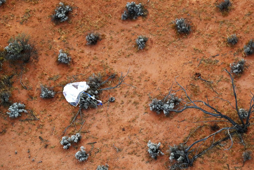 In this photo provided by the Japan Aerospace Exploration Agency (JAXA), a capsule, center, dropped by Hayabusa2 is seen before being retrieved in Woo...