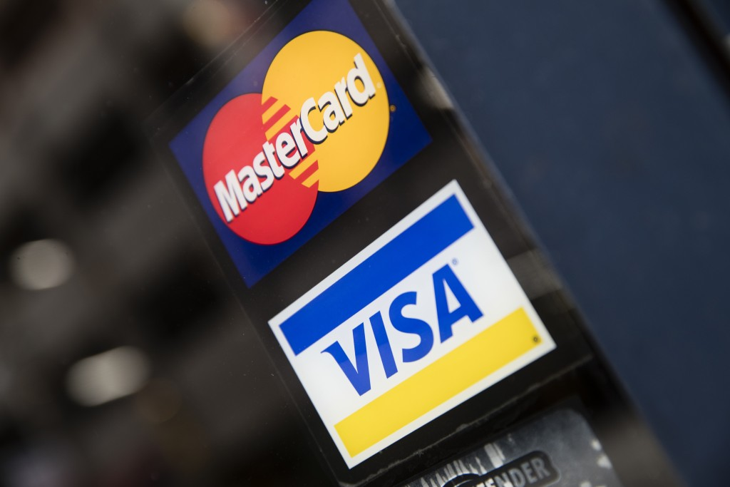 FILE- This Nov. 29, 2018, file photo shows credit card logos posted on a store's door in Philadelphia. The coronavirus pandemic hasn't stopped America...
