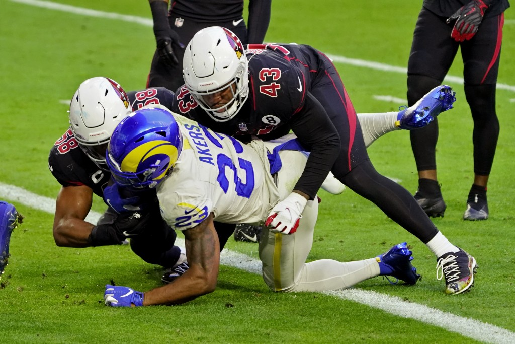 Los Angeles Rams running back Cam Akers (23) scores a touchdown as Arizona Cardinals outside linebacker Haason Reddick (43) and middle linebacker Jord...