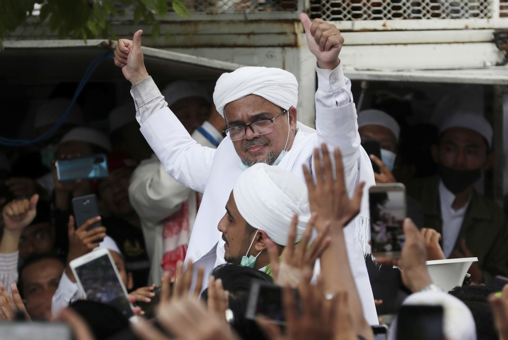 FILE - In this Tuesday, Nov. 10, 2020, file photo, Indonesian Islamic cleric and the leader of Islamic Defenders Front Rizieq Shihab, center, gestures...