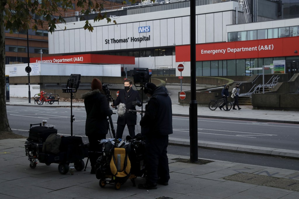 A broadcast news crew reports from outside St Thomas' Hospital in London, which starting this week is going to become one of the hubs for vaccinating ...