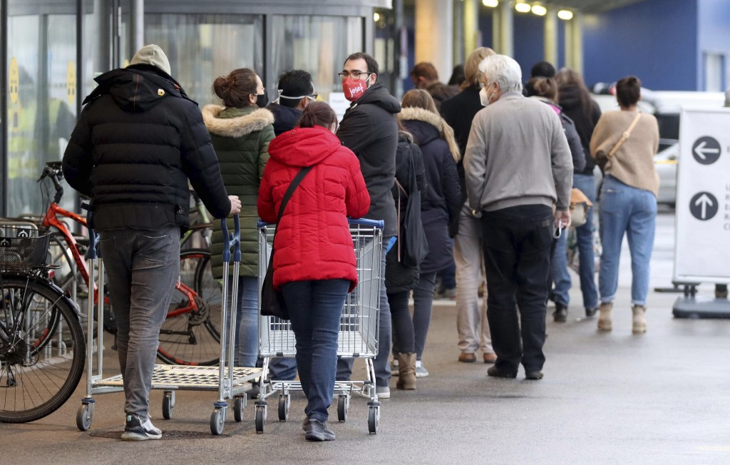 People line up in front of a shop after the stores reopen after a lock down in Vienna, Austria, Monday Dec. 7, 2020., 2020. The Austrian government ha...