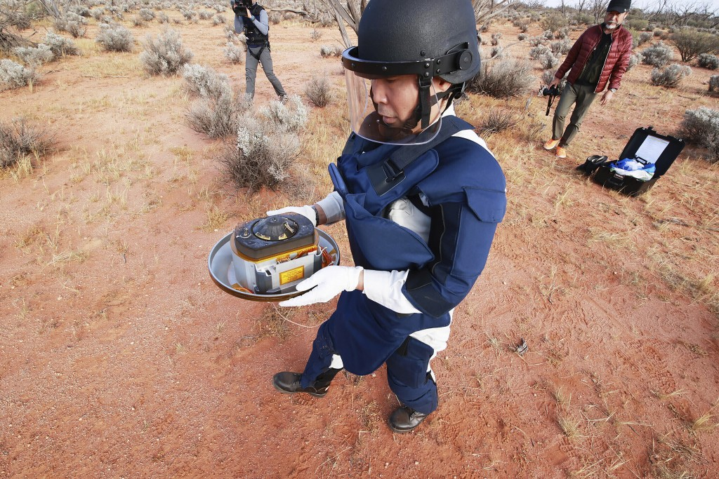 FILE - In this Sunday, Dec. 6, 2020 photo provided by the Japan Aerospace Exploration Agency (JAXA), a member of JAXA retrieves a capsule dropped by H...