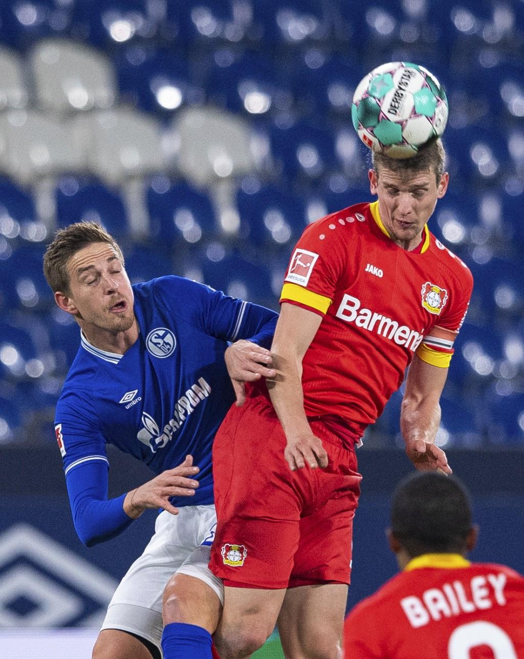 Leverkusen's Lars Bender, right, challenged by Schalke's Bastian Oczipka during their German Bundesliga soccer match at the Veltins Arena in Gelsenkir...