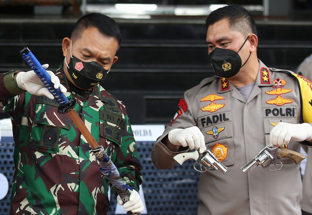 Local police chief Inspector General Fadil Imran, right, and military commander Maj. Gen. Dudung Abdurachman, left, show weapons confiscated from susp...