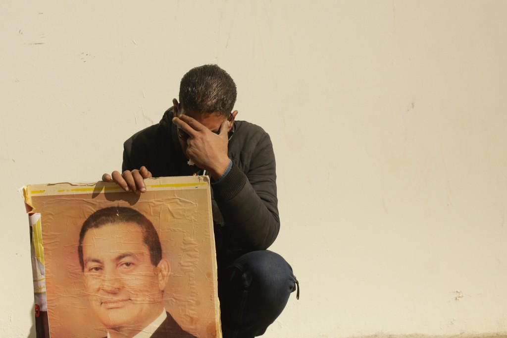 FILE - In this Feb. 26, 2020, file photo, a supporter holds a photo of Egypt's ousted autocratic President Hosni Mubarak as he weeps outside the gate ...