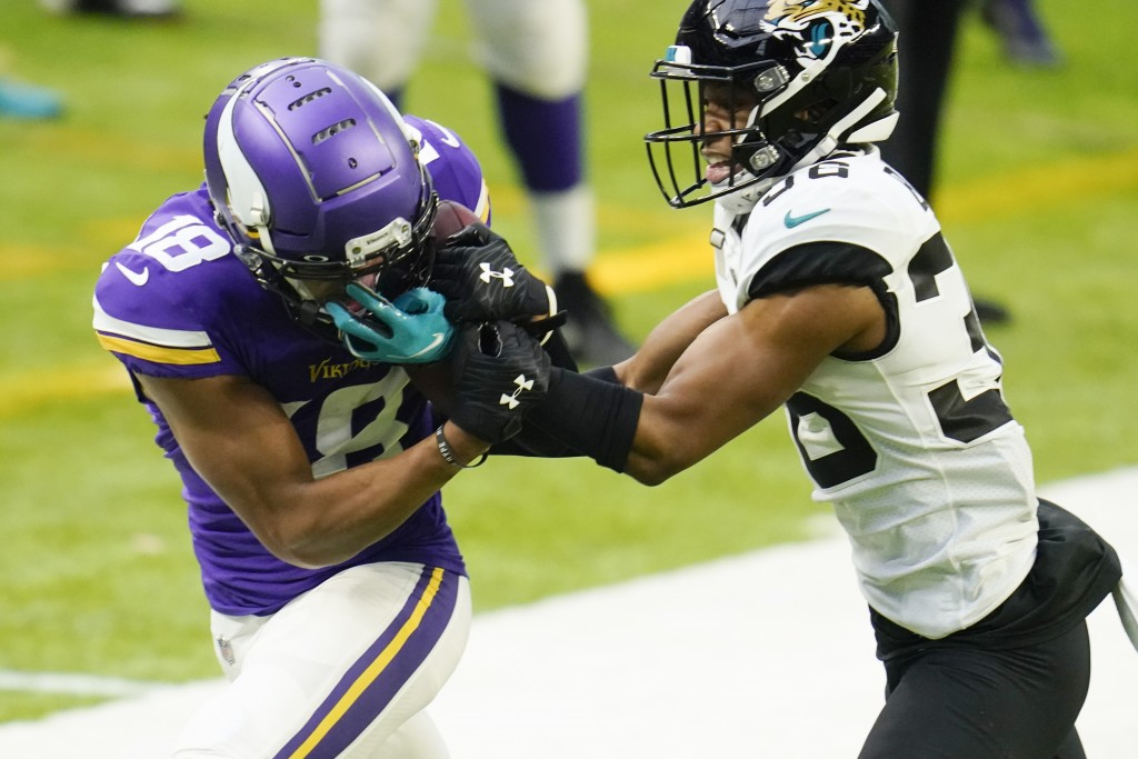 Minnesota Vikings wide receiver Justin Jefferson, left, catches a pass in front of Jacksonville Jaguars cornerback Luq Barcoo, right, during the secon...