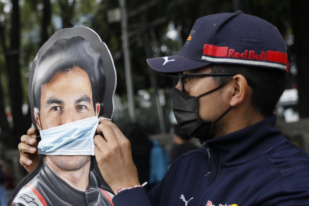 "A man adjusts a face mask on a promotional cardboard cutout of Sergio ""Checo"" Perez, as a small group of fans gathers to celebrate his first Formula O..."