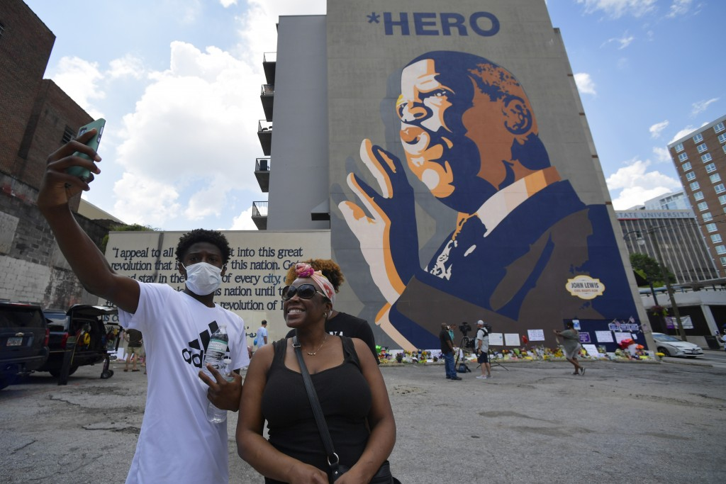 FILE - In this July 19, 2020, file photo, people gather at a makeshift memorial near the home of Rep. John Lewis, D-Ga., in Atlanta. Lewis, who died F...