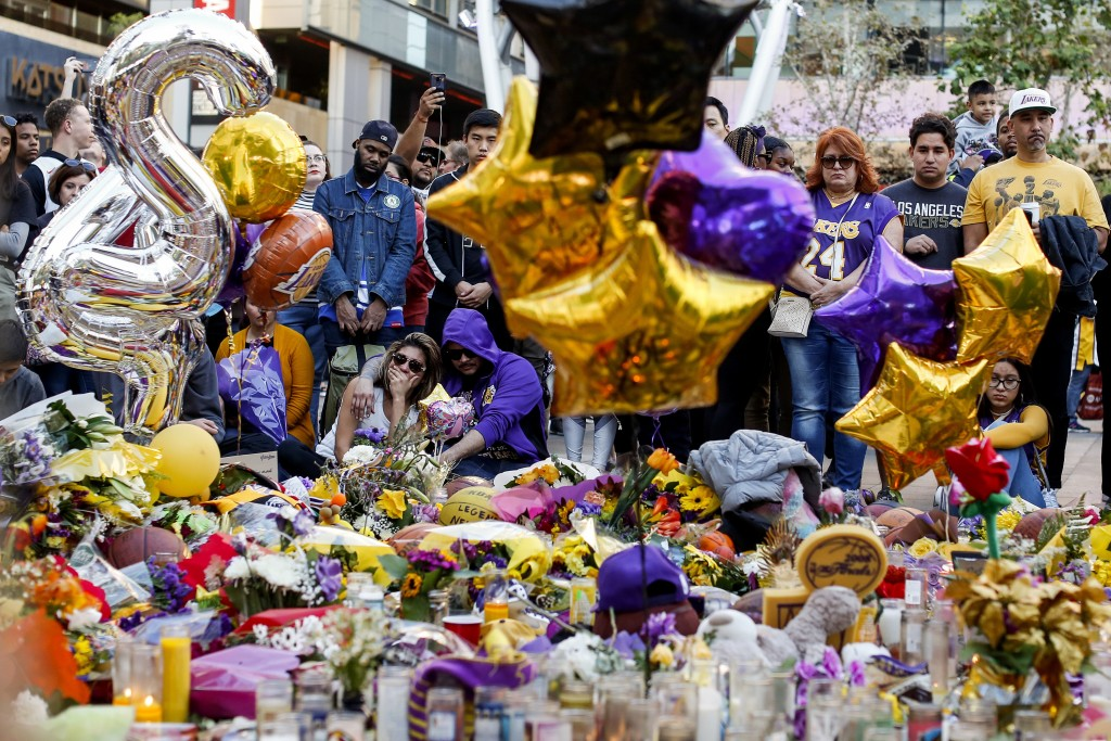 FILE - In this Jan. 28, 2020, file photo, fans pay respect at a memorial for Kobe Bryant near Staples Center in Los Angeles. Bryant, the 18-time NBA A...