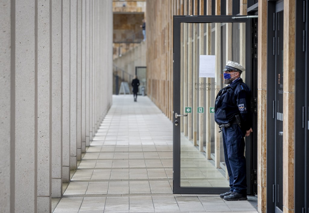 A police officer guards the entrance of a vaccine center that was introduced to the media in Wiesbaden, Germany, Monday, Dec. 7, 2020. The vaccine cen...