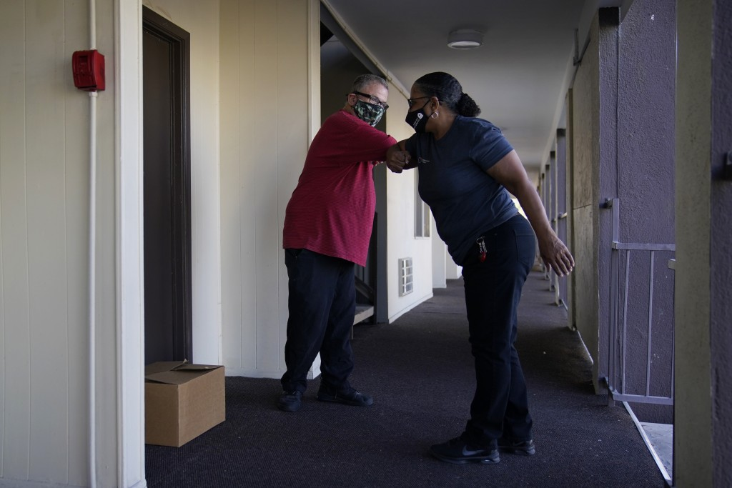 Larry Holt, left, thanks Diana Everett after she delivered a box of food to his apartment, Thursday, Nov. 19, 2020, in Las Vegas. Holt lost his casino...