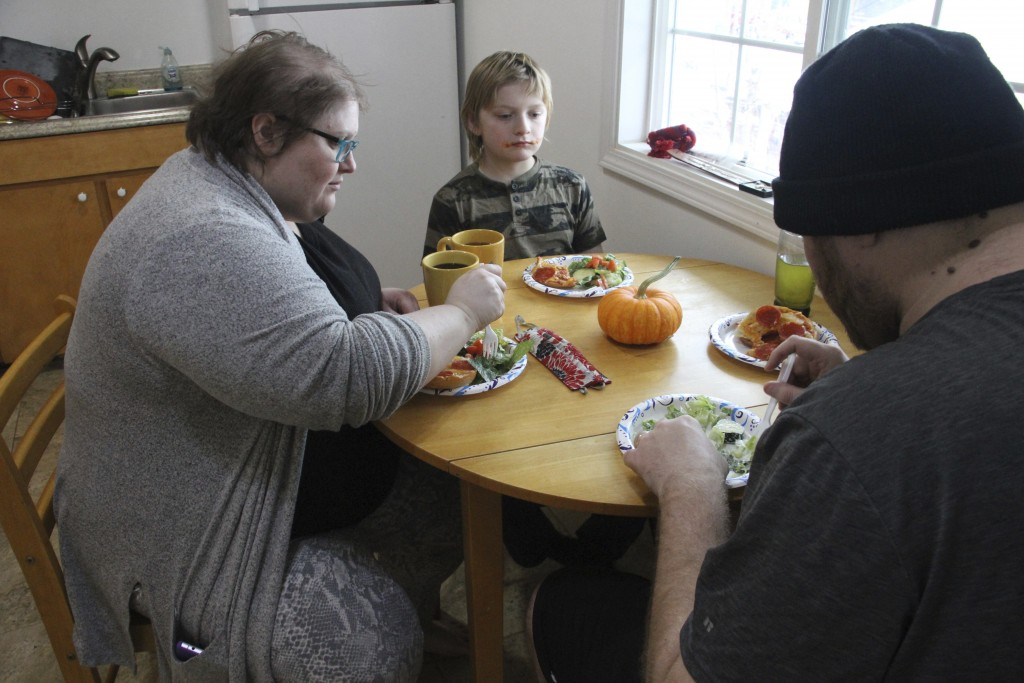 Airis Messick, left, and Brian Messick, right, eat lunch with this 9-year-old son, Jayden, at their apartment in Anchorage, Alaska, on Wednesday, Nov....