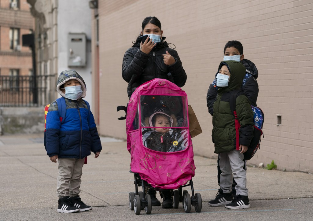 A woman and her children walk to P.S. 134 Henrietta Szold Elementary School, Monday, Dec. 7, 2020, in New York. Public schools reopened for in-school ...