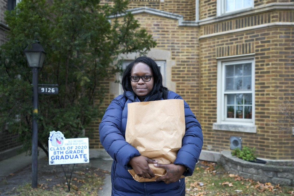 Briana Dominguez poses for a portrait outside her family's apartment building in Skokie, Ill., on Saturday, Nov. 21, 2020, holding the bag of grocerie...