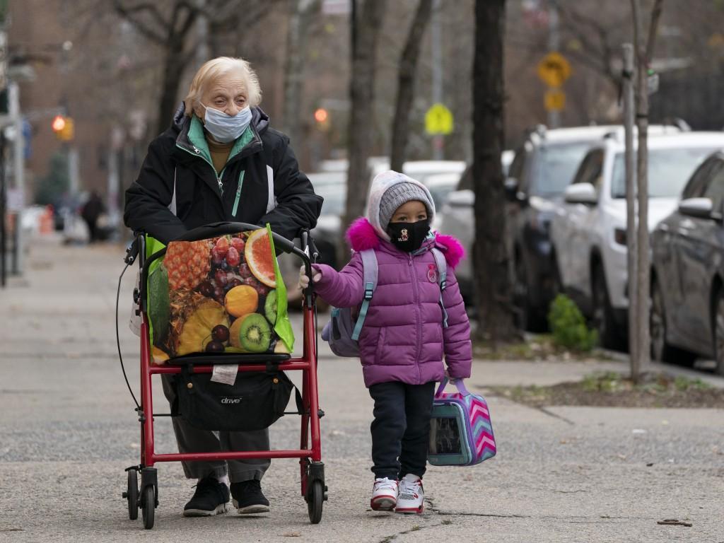 Rose Curto walks her great-great-granddaughter Summer Mejias to P.S. 134 Henrietta Szold Elementary School, Monday, Dec. 7, 2020, in New York. Public ...