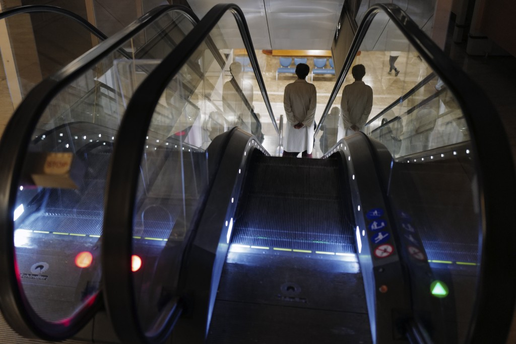 A medical members staff uses the escalator at Bichat Hospital, AP-HP, in Paris, Wednesday, Dec. 2, 2020. One of the biggest hospitals in Paris, Bichat...