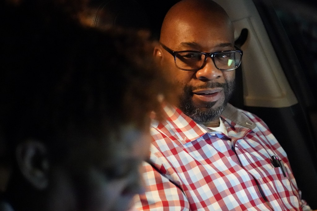 Norman Butler, a first-time food bank user, talks with his girlfriend, Cheryl Butler, as they sit in their car overnight waiting in line at a food dis...