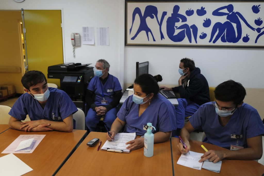 Medical staff, including Dr. Philippe Montravers, second left, attend a morning meeting, at Bichat Hospital, AP-HP, in Paris Tuesday, Dec. 1, 2020. On...
