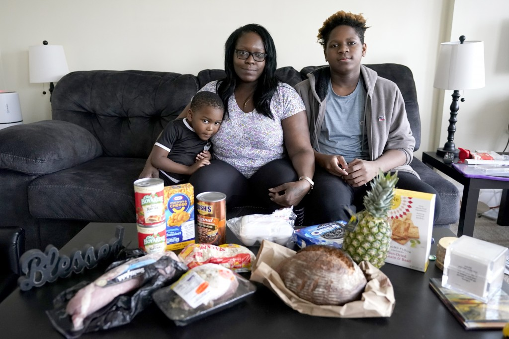 Briana Dominguez, center, sits with her sons, Noah Scott, 4, left, and Nehemiah Powell, 14, for a portrait inside their their Skokie, Ill., apartment ...