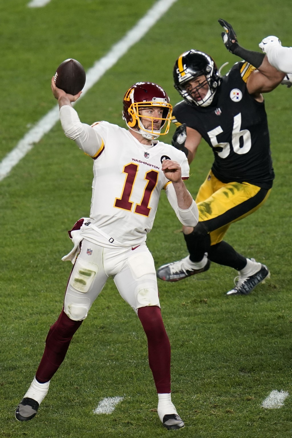 Washington Football Team quarterback Alex Smith (11) gets off a pass under pressure from Pittsburgh Steelers linebacker Alex Highsmith (56) during the...